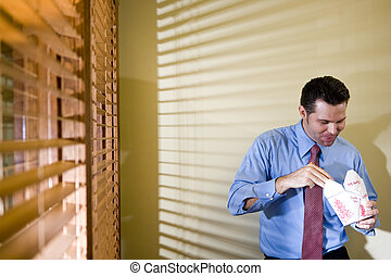 Male office worker eating Chinese takeout - Male office...