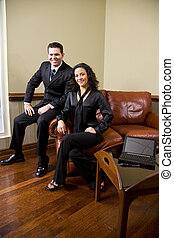 Confident business couple on sofa in office