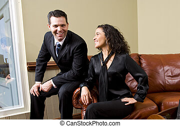 Confident business couple on sofa in office - Hispanic...