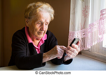 woman typing on the smartphone. - Elderly woman typing on...