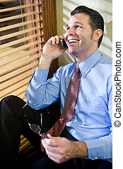 Happy businessman talking on mobile phone