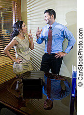 Hispanic office worker working with male colleague - Female...