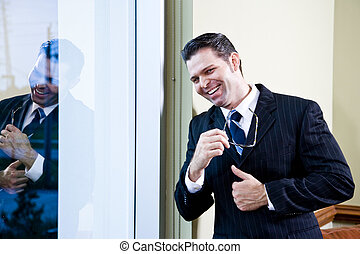 Confident businessman standing in office by window