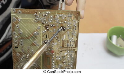 Technician chip with a soldering iron - Close-up of hand...