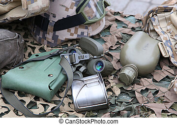 military flask, pot and a binoculars on a camouflage net