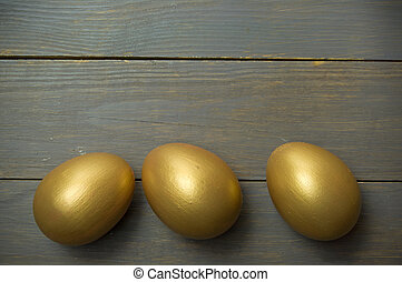Golden eggs - Gold eggs over a wood background