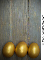 Easter egg background - Golden easter eggs over wood