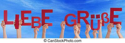 People Holding German Word Liebe Gruesse Means Love Blue Sky...