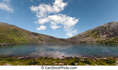 Mountain lake with reflection on the smooth water, timelapse...