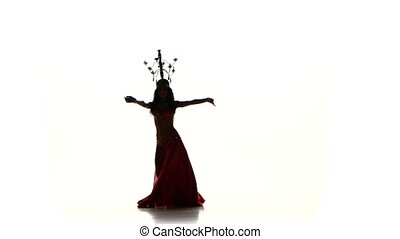 Attractive belly dancer woman dancing with candles on her head and shaking her hips, silhouette, on white