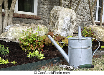 Watering Can - Watering can and trowel nest to landscape...