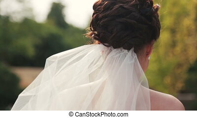 Gorgeous brunette bride looks into the camera close up.