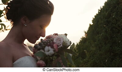 Beautiful bride sniffing the flowers close up.