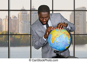 Afro explores globe at daytime. Man with globe in...