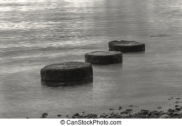 B and W of three objects in water - A BW of three round...