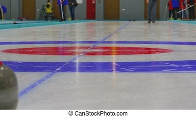 The player rolls a curling stone - Curling player delivering...