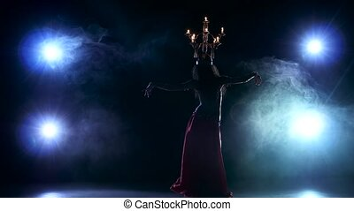 Beautiful belly dancer go on dancing with candles, her head, black, smoke, silhouette