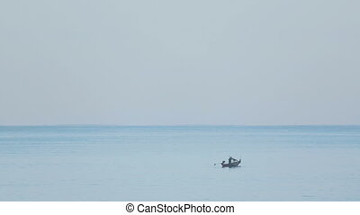 Longtail fishing boat in the ocean in the early morning