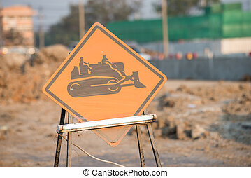 warning sign of construction vehicles on the road