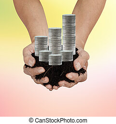 Saving Coins Wealth - soil in palm hands with silver coin...