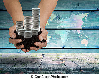 Money Saving Concept - soil in palm hands with silver coin...