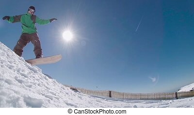Snowboarder jumping against blue sk - Snowboarder executing...