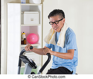 matured asian male on exercise bike