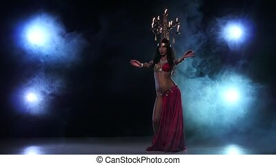 Belly dancer girl dancing with candles, her head, black, smoke, slow motion