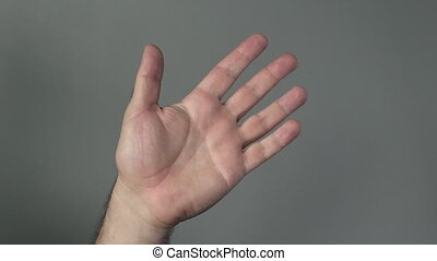 Man hand wave hello on a grey background. Concepts and ideas...