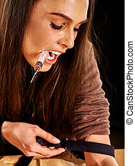 Female drug addict with syringe tighten tourniquet. - Female...