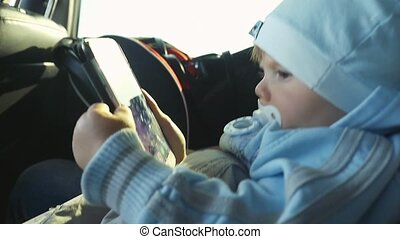 Toddler boy playing smartphone in the car in slowmotion at...