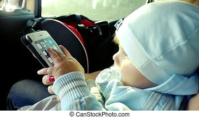 Toddler boy playing smartphone with mom in the car in...