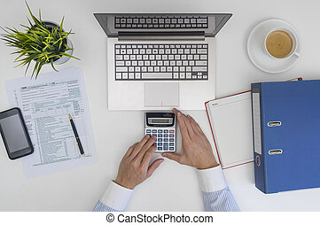 Businessman making calculation and filling tax form at...