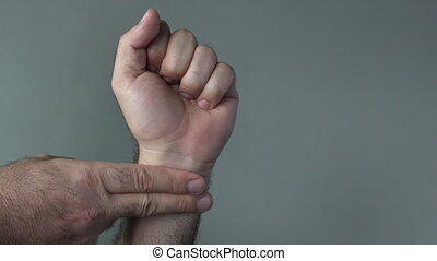 Man hands checks self pulse on a grey background. Concepts...