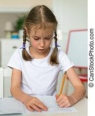 Cute little girl doing her homework for school.