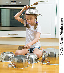 Little girl playing drums on pots and pans in the kitchen.