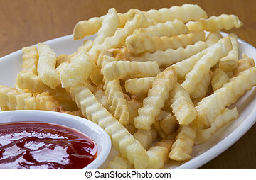 Delicious crinkle cut style french fries with ketchup - A...