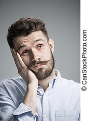 Man is looking bored Over gray background - Man wearing a...