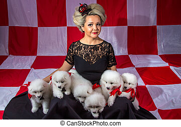 Smiling woman with white puppies on plaid background