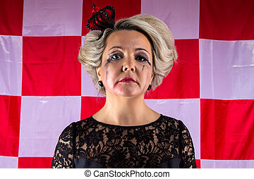 Sad woman with crown in hysterics on plaid background
