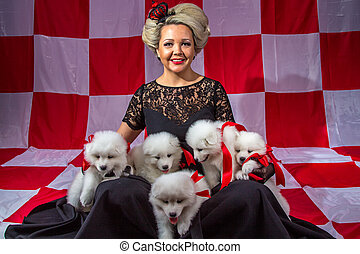 Happy woman with white puppies on plaid background
