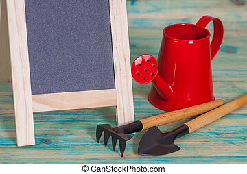 garden tool and red watering can.
