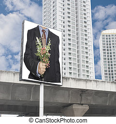 business man hand hold a flowers bouquet on billboard