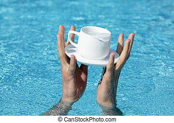 two hands saving a cup and saucer