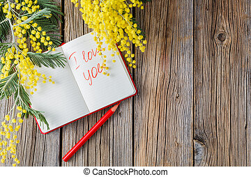 rural wooden table with notebook and love message, yellow...