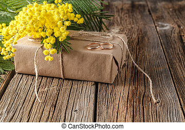 Wedding gift wrapped in craft paper with spring yellow...