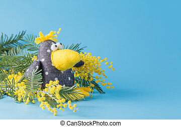 Kid toy crow with spring flowers on blue background