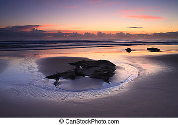 Sunrise reflections on the beach - Sunrise reflections in...