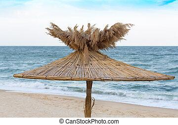 Straw umbrellas on sunny beach in Bulgaria