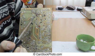 A technician working on a chip with a soldering iron